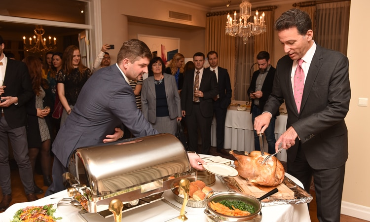 Ambassador Adam Sterling carves Thanksgiving turkey (Embassy photo)